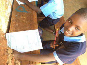 student-taking-midterms-school-slums-Uganda